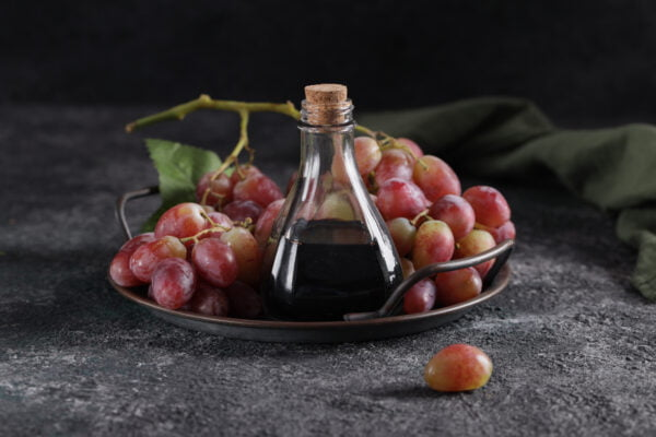 balsamic vinegar in a glass bottle and fresh grapes