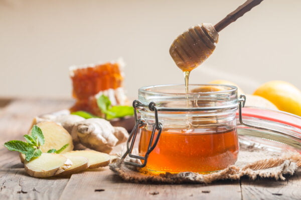 Honey in jar with ginger and lemon
