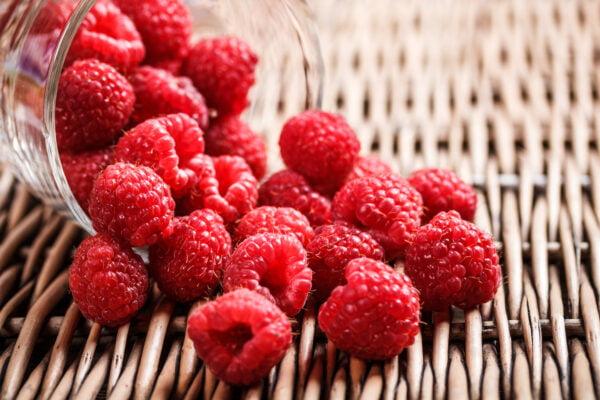 Raspberries scattered on wicker tray